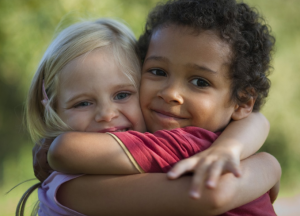 two young children who are visually different are hugging